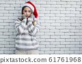 Young woman in costume Christmas on white brick 61761968