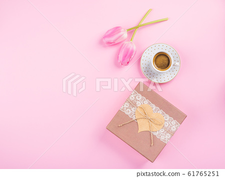Cup coffee, gift box and tulips on pink backdrop 61765251