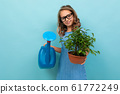 Schoolgirl with wavy brown hair in blue dress with eyeglasses is watering a flower isolated on blue 61772249