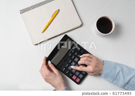 Flat lay. Women's hands and calculator near 61773495