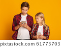 Image of young woman spying and peeking at smartphone of her boyfriend isolated over yellow background 61773703
