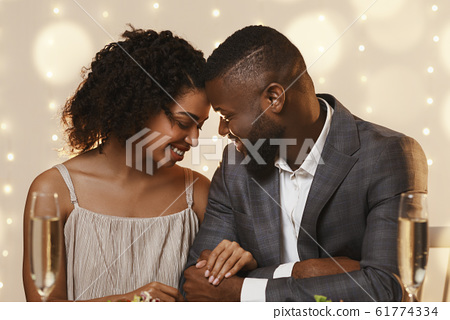 Afro couple in love cuddling at restaurant while having date 61774334