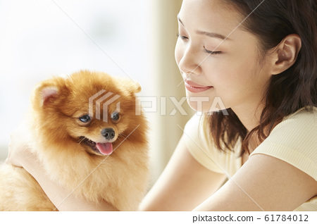 Young woman living with small dog 61784012