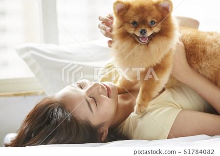 和小狗一起生活的年輕女子 61784082