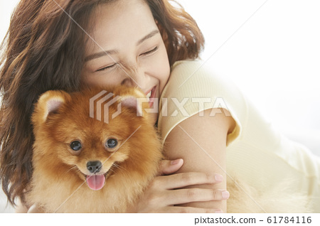 Young woman living with small dog 61784116
