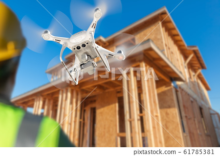 Pilot Flies Drone Quadcopter Inspecting Home 61785381