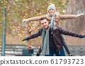 Young dad and adorable little girl have fun on skating rink outdoors 61793723