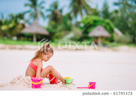 Adorable little girl playing with beach toys during tropical vacation 61795378