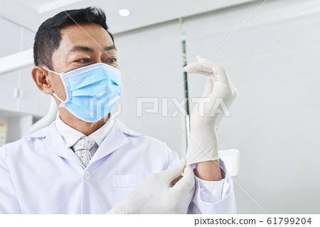 Dentist Putting On Latex Gloves 61799204