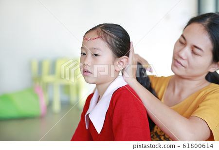 Close-up Asian mom combing her daughter hair at 61800614