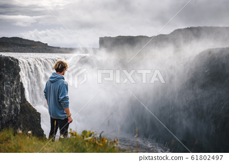 Hiker standing at the edge of the Dettifoss waterfall in Iceland 61802497