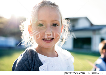 Front view of small girl standing outdoors, looking at camera. 61806755