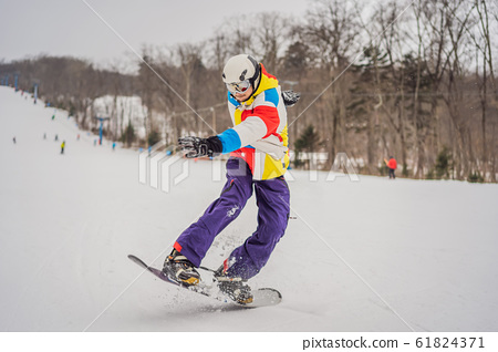 Young man jumping with a snowboard in the mountains 61824371