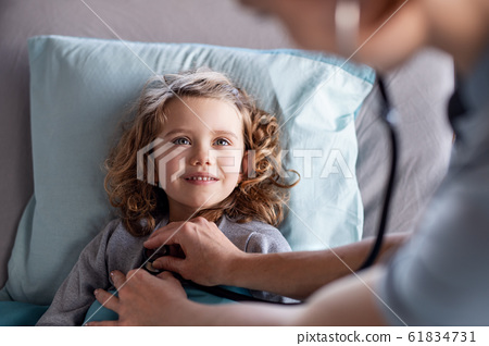 Unrecognizable female doctor examining small girl in bed in hospital. 61834731
