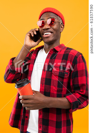 portrait of a black american handsome stylish man wearing a checkered reddish shirt holding a drink 61837590