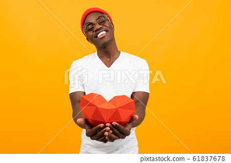Cute handsome African man with a beautiful smile in a white T-shirt holds out a red 3D heart made of 61837678