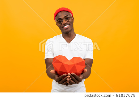 cute handsome african man in a white t-shirt holds out a red 3d heart made of paper for valentines 61837679