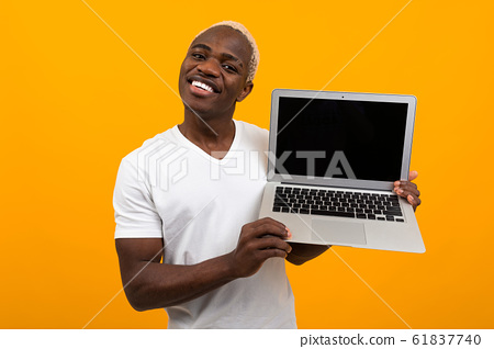 handsome african man with pretty smile holds laptop wireless computer with mock up on yellow 61837740