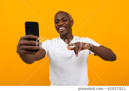 handsome black american man taking selfie on phone and smiling over orange background 61837821