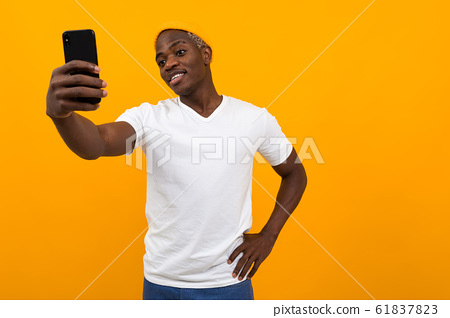 handsome black african man makes selfie on the phone on an orange background with copy space 61837823