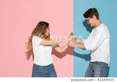 Young emotional man and woman on pink and blue background 61844454