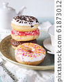 Four variegated sweet donuts and teapot for breakfast  61873012