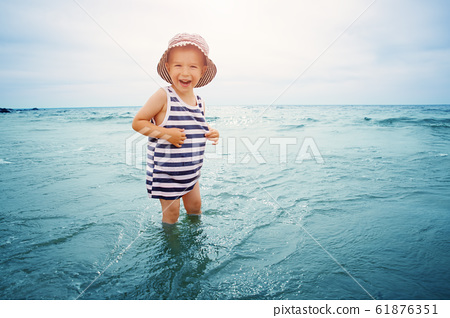 three years old boy playing at the beach in the water 61876351