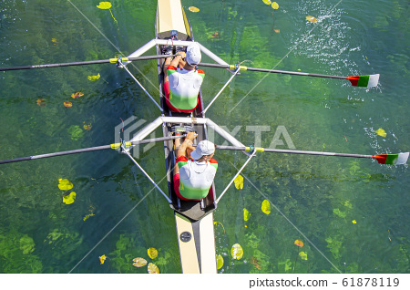 Two young athletes rowing team on green lake 61878119