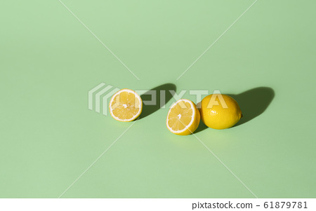 Fresh lemons cut in half on a green background. 61879781