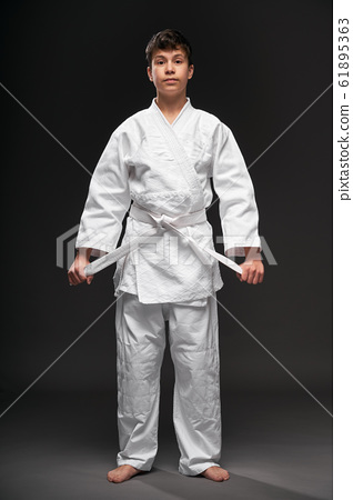a teenager dressed in martial arts clothing poses 61895363