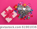 Gift in a pink box on crimson background and wicker decorative heart beside. Gift box with wicker heart beside surrounded with coloured hearts. Heart shaped gems 61901036