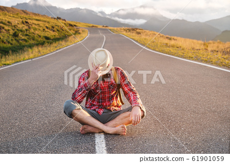 Stylish barefoot bearded male hitchhiker traveler in a hat and with a backpack sits on a suburban asphalt road in the mountains at sunset and waits for cash assistance looking to the sky. 61901059