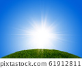 Meadow bathed in a refreshing blue sky and light 61912811