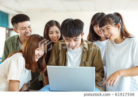 excited college students looking at laptop  in 61917506