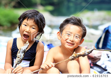 Children eating river fish 61918703