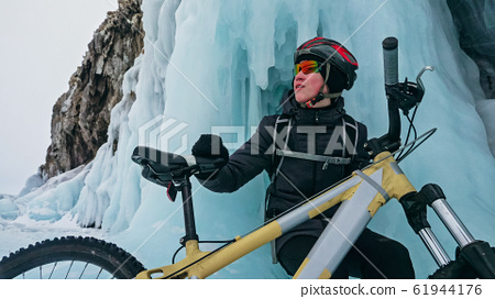 Man is riding bicycle near ice grotto. Rock with ice caves icicl 61944176