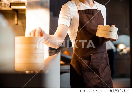 Caucasian barman waiting for order near the kitchen 61954265