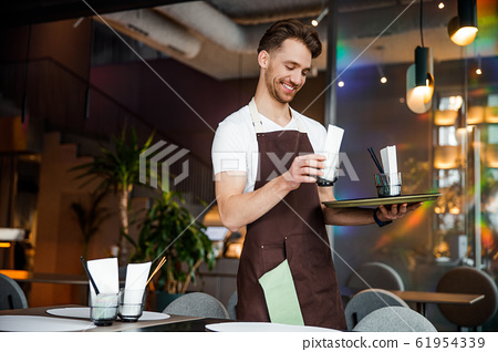 Happy waiter in apron enjoying his job 61954339
