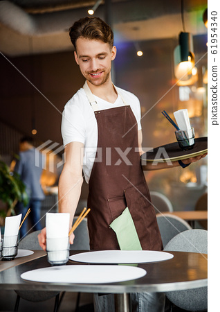 Bearded waiter in apron lays the table in cafe 61954340