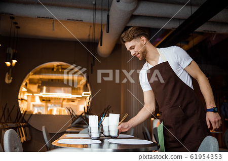 Young atrractive waiter lays the table in cafe 61954353