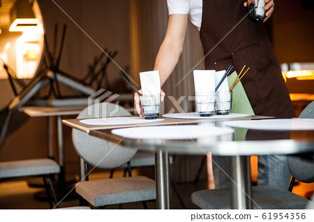 Caucasian waiter lays the table in cafe 61954356