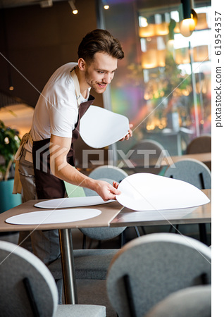 Handsome waiter lays the table in cafe 61954357