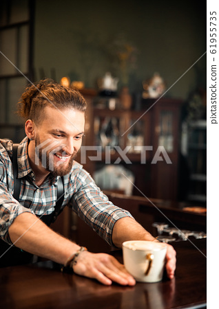 Smiling young male barista is working in coffee shop 61955735