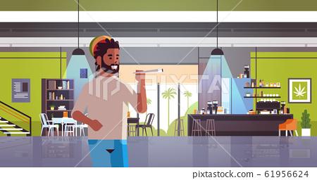 african american guy smoking marijuana joint rastaman relaxing with weed cigarette coffeeshop interior portrait horizontal 61956624