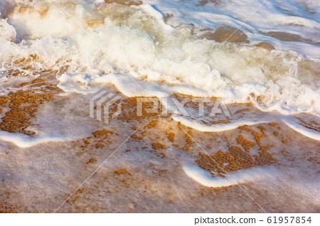 sea waves splash foam on the sunny beach 61957854