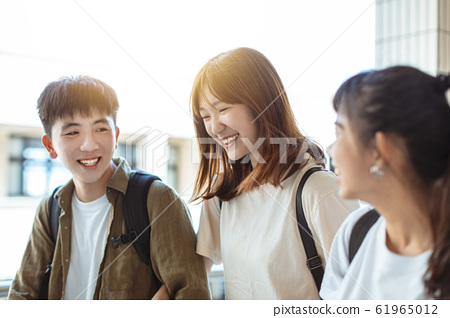 Group of happy students walking along the corridor 61965012