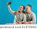 Twin Brothers Taking Selfie 61976682