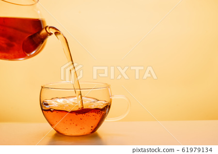 Tea being poured into glass tea cup 61979134