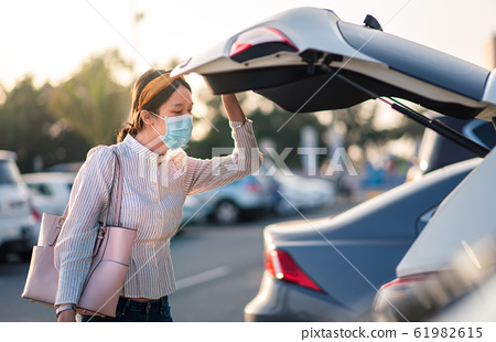 Asian girl wearing face mask at a parking lot 61982615