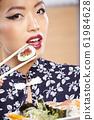 beautiful asian woman eating sushi with chopsticks 61984628